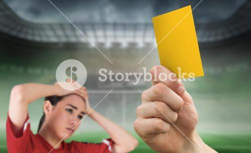 Composite image of hand holding up yellow card to fan