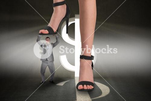 Composite image of female feet in black sandals stepping on tiny businessman
