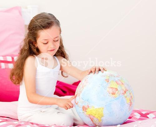 Adorable little girl holding a terrestrial globe sitting on her bed