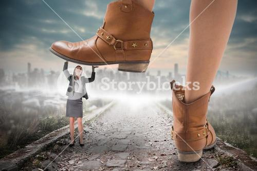 Composite image of cowboy boots stepping on businesswoman