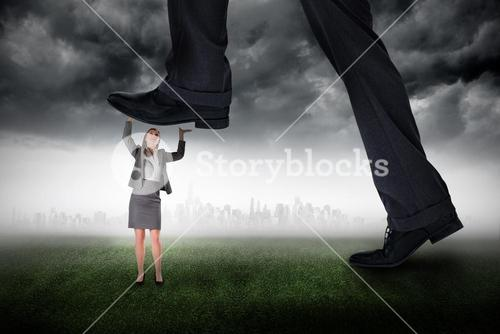 Composite image of businessman stepping on tiny businesswoman