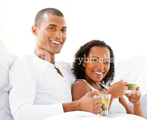 Happy couple drinking a cup of tea lying on their bed