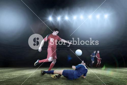 Composite image of football players tackling for the ball