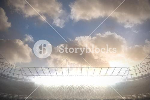 Large football stadium with spotlights under blue sky with clouds