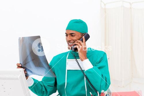 Smiling doctor on phone examining an xray