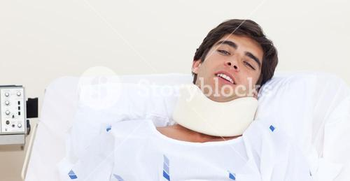 Male patient with a neck brace lying on a bed
