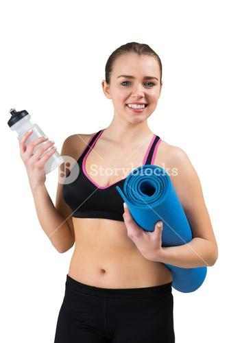 Fit brunette holding mat and sports bottle