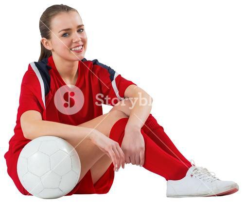 Cute football player sitting with ball