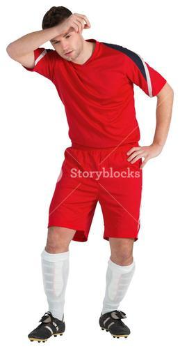 Football player in red wiping his brow
