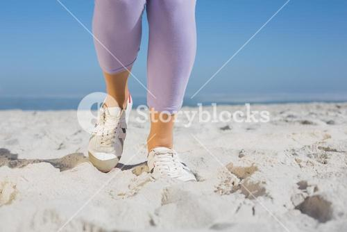 Sporty womans feet on the sand