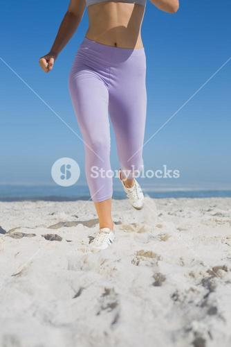 Sporty womans legs on the sand