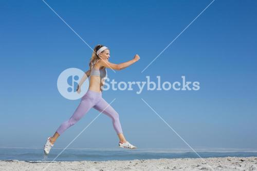 Sporty blonde leaping on the beach