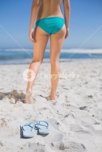 Rear view of fit woman in bikini on beach with flip flops on sand