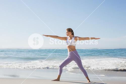 Sporty blonde in warrior pose on the beach