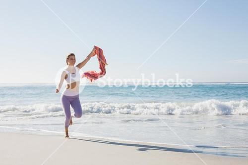 Sporty blonde jogging on the beach with a scarf