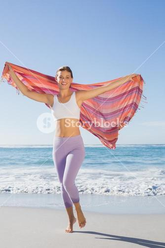 Sporty blonde standing on the beach with a scarf