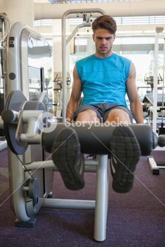 Focused man using weights machine for legs