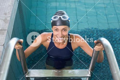 Fit swimmer smiling at camera getting out of the swimming pool