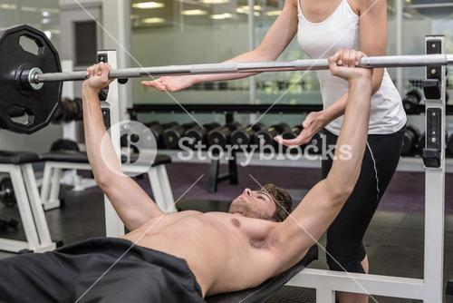 Fit shirtless man lifting barbell with his trainer spotting
