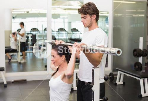 Fit woman lifting barbell with her trainer spotting