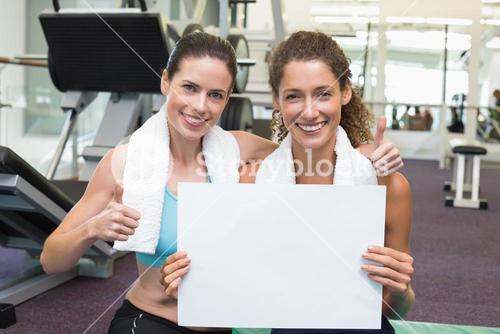 Fit friends showing white card to camera