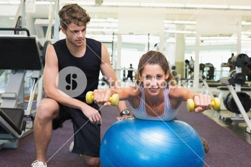 Trainer watching client balance on exercise ball with dumbbells