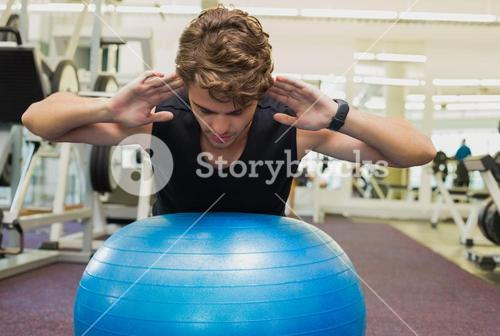 Fit man balancing on exercise ball