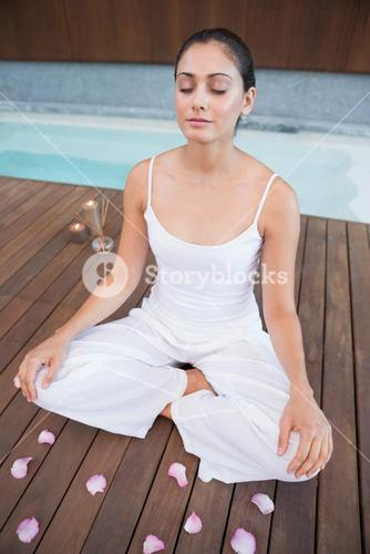 Peaceful brunette in white sitting in lotus pose surrounded by petals