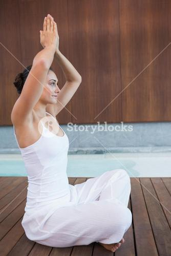 Content brunette in white sitting in lotus pose with hands together