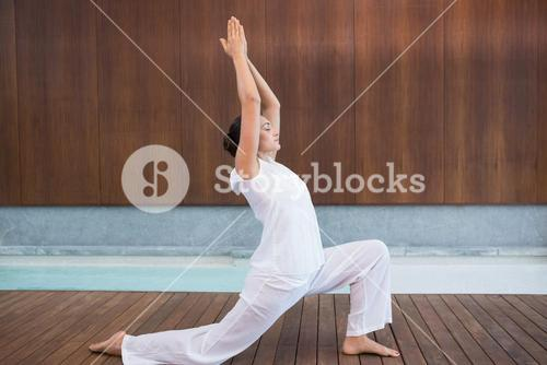 Content brunette in white doing tai chi