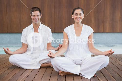 Attractive couple in white sitting in lotus pose smiling at camera