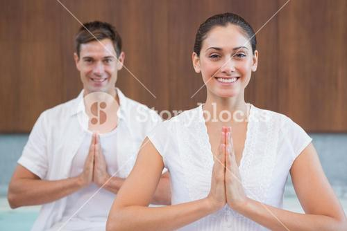 Smiling couple in white sitting in lotus pose with hands together