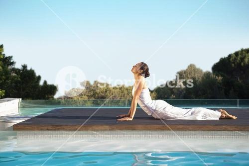 Peaceful brunette in cobra pose poolside