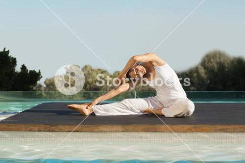 Peaceful brunette in janu sirsasana yoga pose poolside