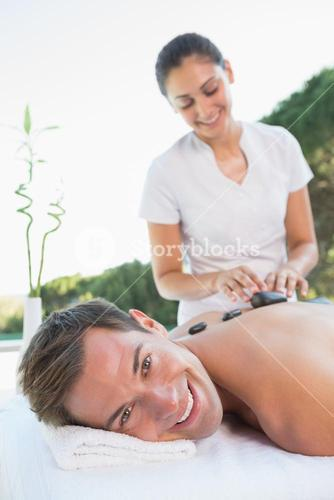 Handsome man getting a hot stone massage poolside