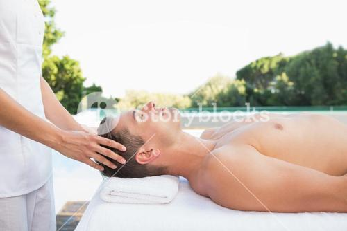 Peaceful man getting a head massage poolside