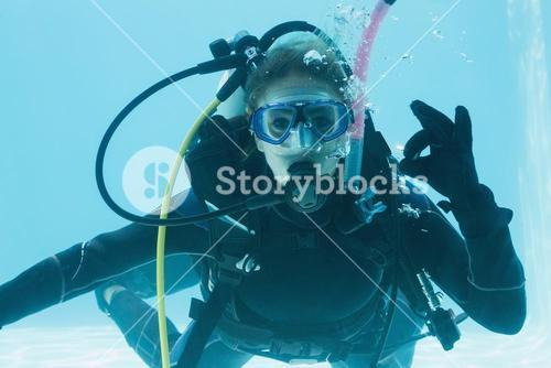 Woman on scuba training submerged in swimming pool making ok sign