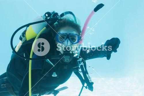 Woman on scuba training submerged in swimming pool showing thumbs down