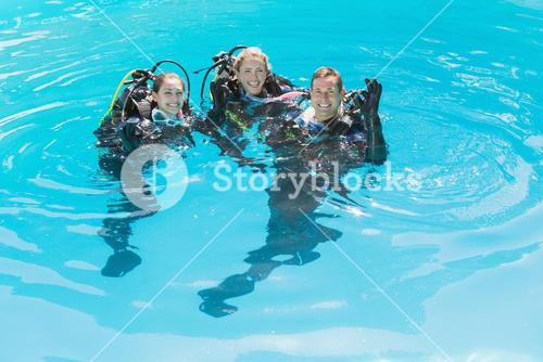 Smiling friends on scuba training in swimming pool