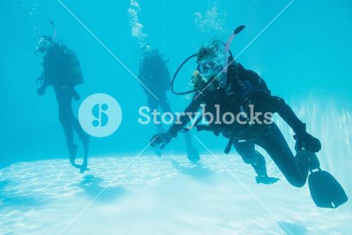 Friends on scuba training submerged in swimming pool one looking to camera