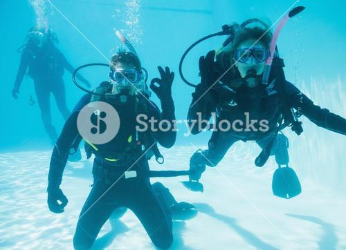 Friends on scuba training submerged in swimming pool two looking to camera