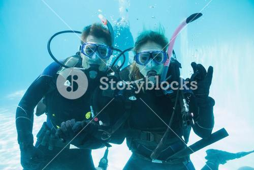 Friends on scuba training submerged in swimming pool looking to camera