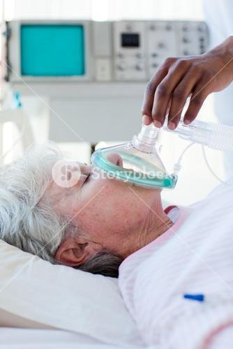 A doctor putting oxygen mask on a patient