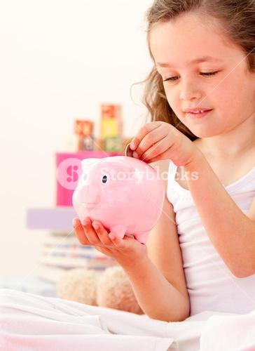 Cute little girl saving money in a piggybank sitting on her bed