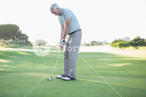 Golfer putting ball on the green