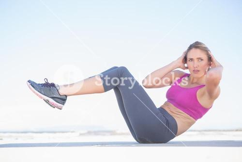 Fit blonde sitting in boat position on the beach