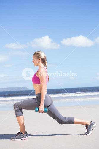 Fit woman working out with dumbbells on the beach lunging