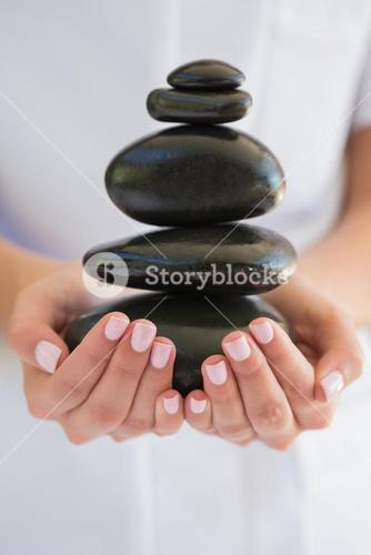 Beauty therapist holding pile of stones for massage