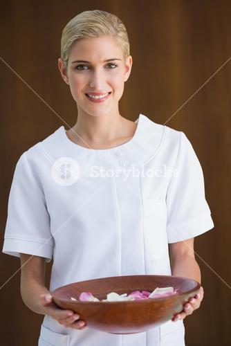 Smiling beauty therapist holding bowl of rose petals