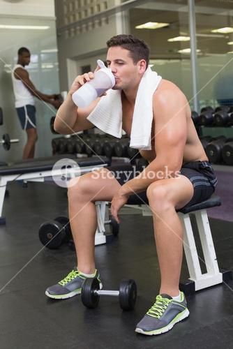 Shirtless bodybuilder holding protein drink sitting on bench
